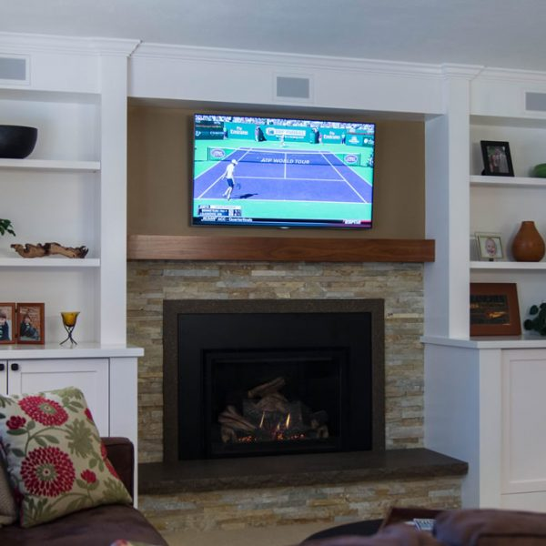 white built-in cabinetry and fireplace with stacked stone surround