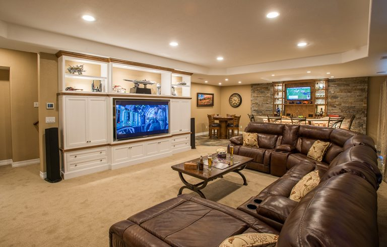 overview of basement finish with custom entertainment center and wet bar
