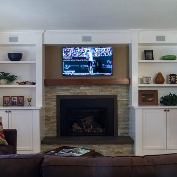 overview of family room with white painted built-in cabinetry and fireplace