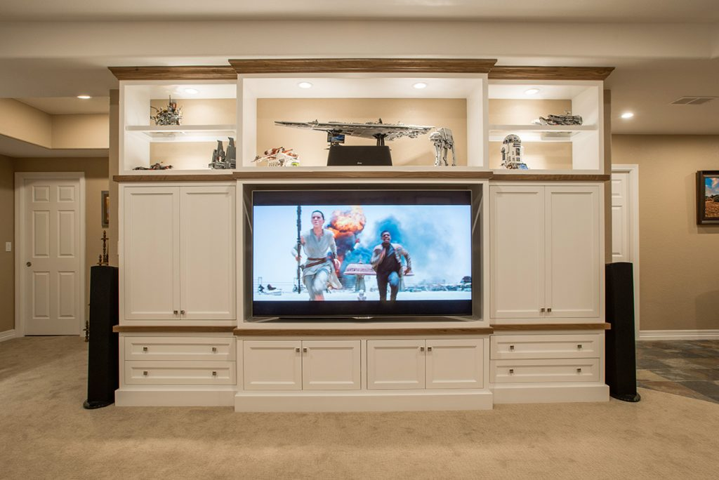 custom white painted entertainment center with walnut trim holds 70-inch TV