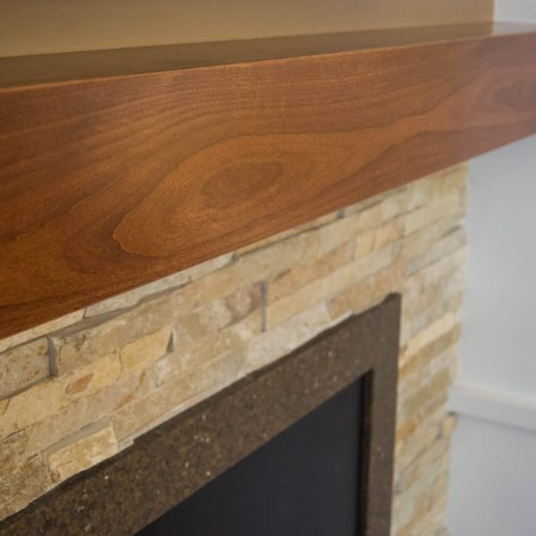 detail of custom alder mantle and stacked stone fireplace surround