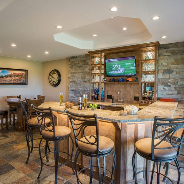 overview of custom wet bar with walnut cabinetry and cork highlights and leathered granite countertop