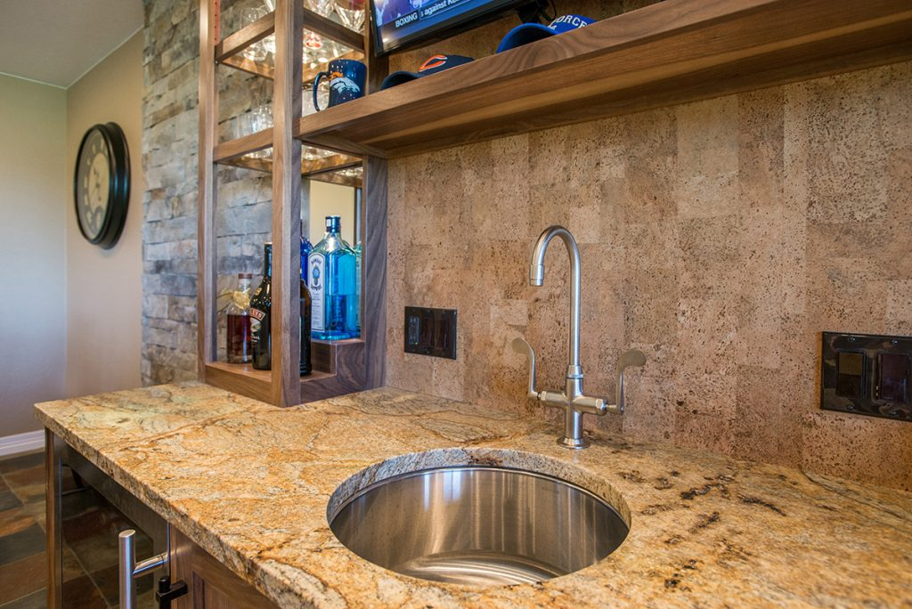 closeup of custom wet bar with walnut cabinetry and cork backsplash and leathered granite countertop