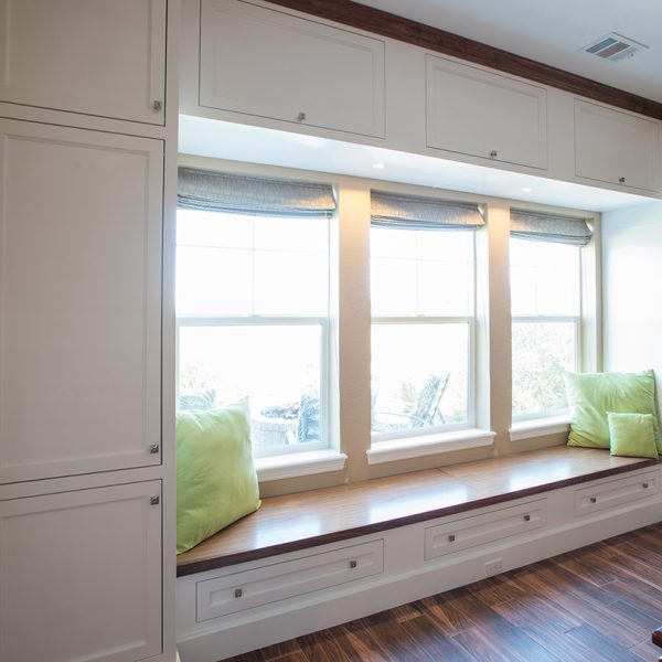 overview of custom walnut window seat with white painted built-in cabinetry