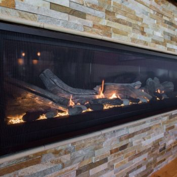 majestic aura linear 70-inch fireplace with stacked stone surround