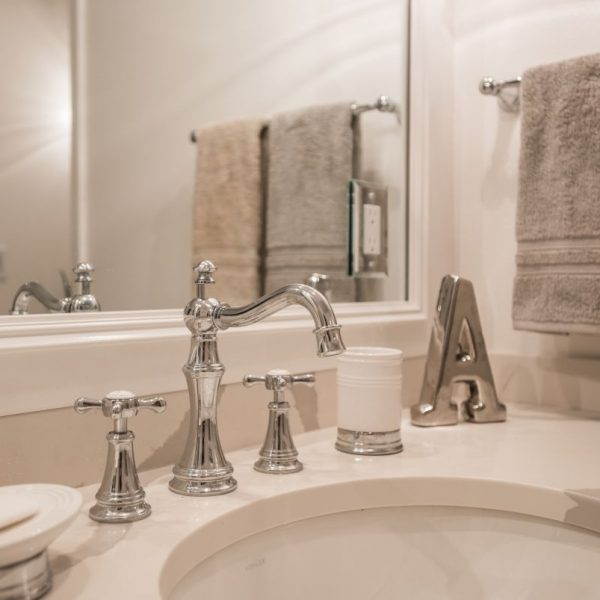 close up of bathroom sink faucet and white countertop