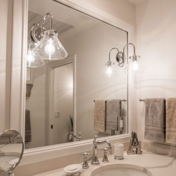 white bathroom countertop and custom white painted mirror frame